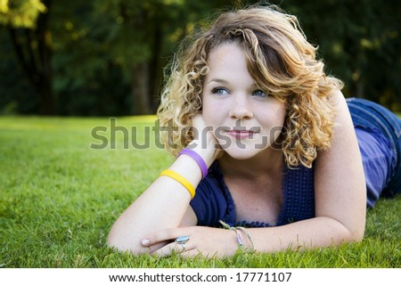 A girl lost in a daydream on the grass - stock photo