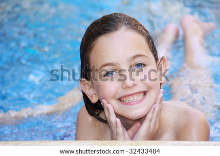 a girl lying down in a swimming pool with splashes of water on her face looking at the camera smiling - stock photo