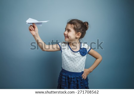 a girl of seven European appearance brunette holding a paper airplane on a gray background, happiness, laughter - stock photo