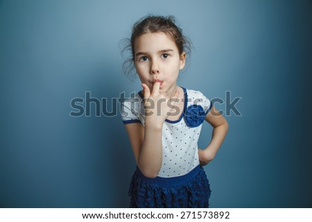 a girl of seven European appearance brunette stuck his index finger in his mouth on a gray background, licking, sucking thumb - stock photo