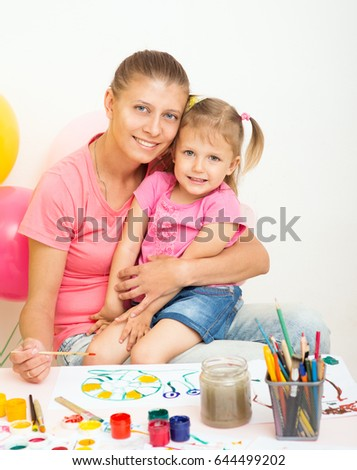 A girl of three years of age draws with her mother