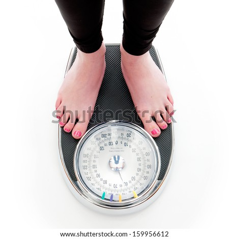 a girl on a weighing scale, on a white background - stock photo