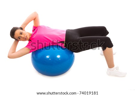 a girl performing an ab crunch on a blue gym ball - stock photo