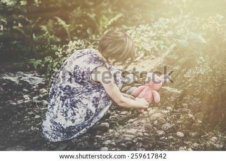 A girl plays with a plush bunny rabbit toy outside in a garden during an Easter party. Part of series.  Filtered for a retro, vintage look. - stock photo