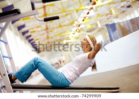 A girl pumping abdominal muscles in gym - stock photo
