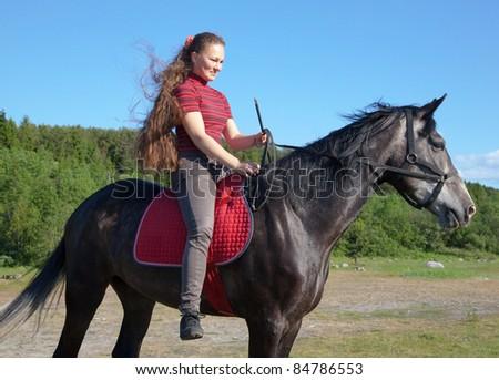 A girl riding a horse on a meadow - stock photo
