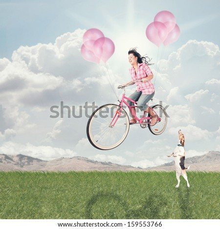 a girl riding her balloon bike in the sky vintage toned - stock photo
