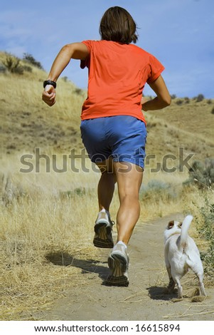 a girl running with her little white dog - stock photo