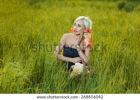 A girl sits among the tall grass in the meadow. - stock photo