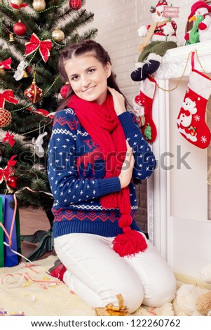 a girl sits near a fire-place
