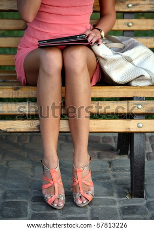 A girl sitting on a bench and reading a book - stock photo