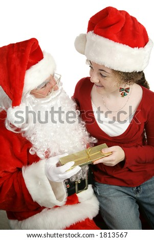 A girl sitting on Santa's lap and getting a gift.