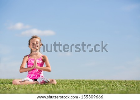 A girl sitting on the green grass in lotus pose with eyes closed - stock photo