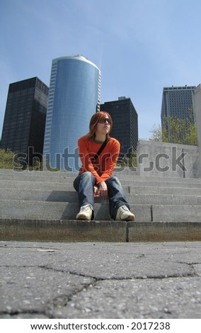 A girl sitting on the stairs of the Battery Park in New York's Financial district.