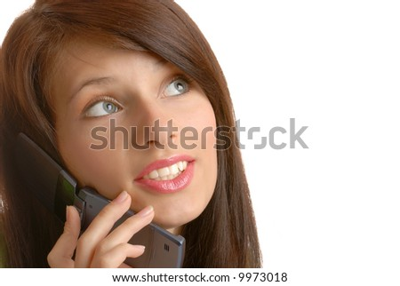 A girl smiles as she listens to someone talking on a phone.