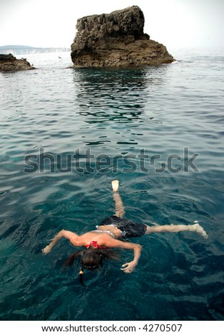 a girl snorkels at the tremiti islands, italy - stock photo