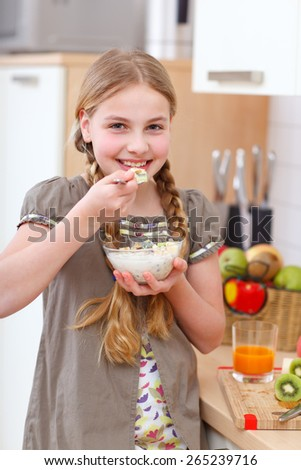 a girl standing in the kitchen and holding a bowl of cereals - stock photo