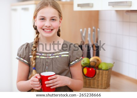a girl standing in the kitchen and holding a cup