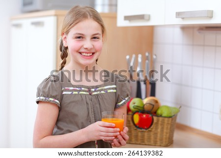 a girl standing in the kitchen and holding a glass with juice