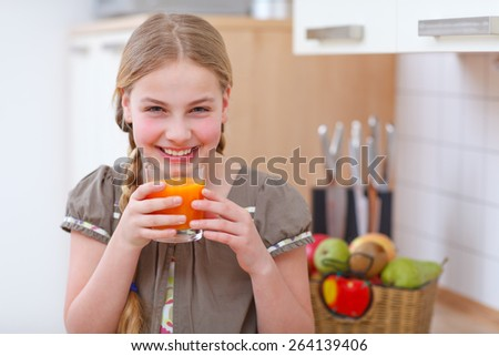 a girl standing in the kitchen and holding a glass with juice - stock photo