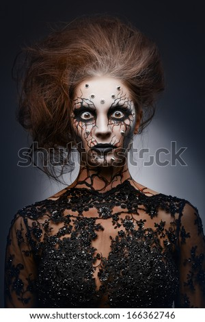 A girl standing like a statue in a creepy halloween costume of a witch with peircing and cracked face paint. Creepy statue. - stock photo