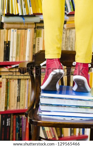 A girl standing on top of a stack of books - stock photo