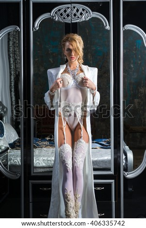 A girl stands in front of a mirror in an expensive lingerie - stock photo