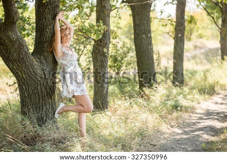 A girl stands in the oak alley and relies on the trunk of an old oak. The wind blew her hair and light dresses. Fain art film. - stock photo