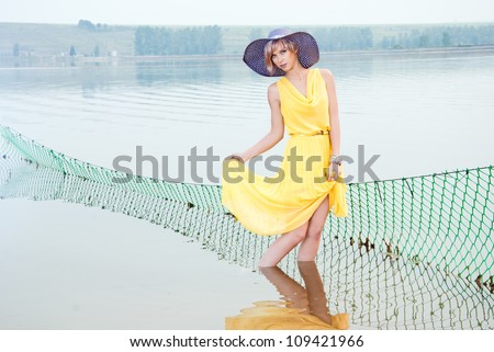 A girl stands in the water near the fishing nets - stock photo