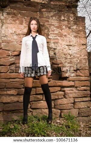 A girl stands near the old wall
