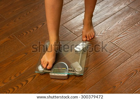 A girl stands on floor scales for weighing.