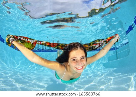 A girl swimming with a colorful scarf underwater - stock photo