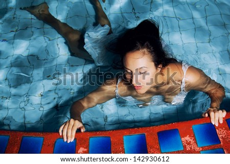 A girl swims in the pool at night - stock photo