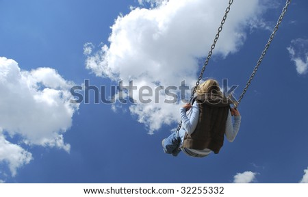 A girl swinging on a swing with blue sky and cloud background. - stock photo