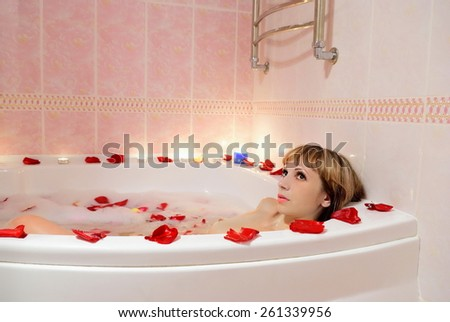 A girl takes a bath in the foam and in the rose petals - stock photo