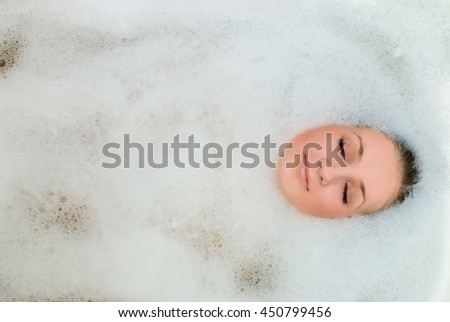 A girl takes a bath in the foam. Foam can see the face - stock photo