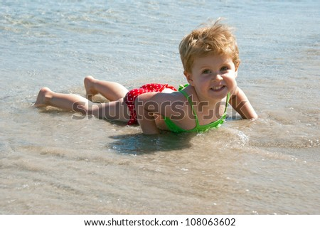 A girl takes fun laying in the sea