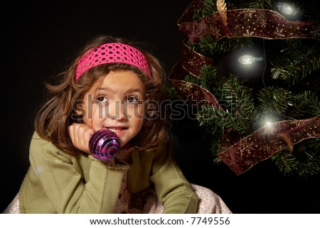A girl thinking nearby a christmas tree holding a christmas ball.