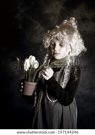 A girl touching the leaf of a plant.