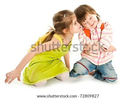 A girl tries to kiss her sister or brother - stock photo