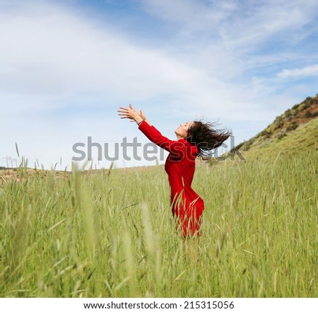 a girl walking in a field letting go - stock photo