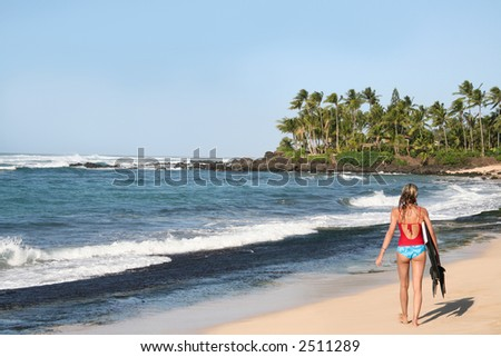 A girl walking on the beach with a bodyboard - stock photo