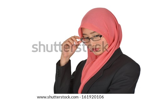 a girl wearing a hijab looks down while holding glasses - stock photo