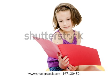 A girl wearing a purple top and jean shorts reading from a folder.