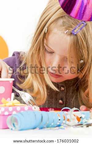 A girl wearing party items eating some food. - stock photo