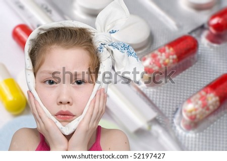 a girl with a bandage around her face, various pills and a glass thermometer in the background - stock photo
