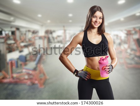 A girl with a bottle in the gym  - stock photo