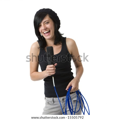 A girl with a mic smiles and sings - stock photo