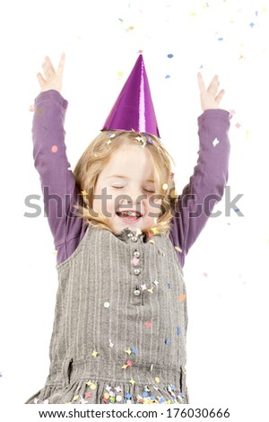 A girl with a party hat and her arms in the air with confetti falling.