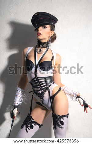 A girl with a perfect waist, in white lingerie and cap standing on a white background with a whip